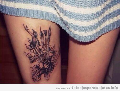 Tatuaje para mujer en las piernas, pinceles y leyenda en el muslo